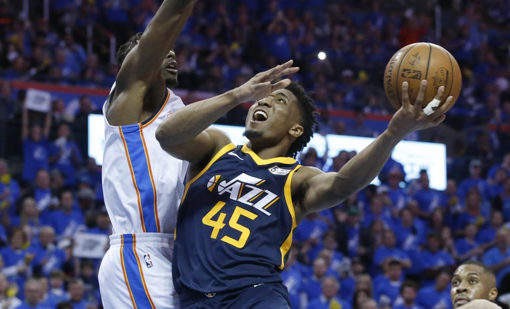 Utah Jazz guard Donovan Mitchell (45) shoots as Oklahoma City Thunder forward Jerami Grant, left, defends in the second half of Game 1 of an NBA baske