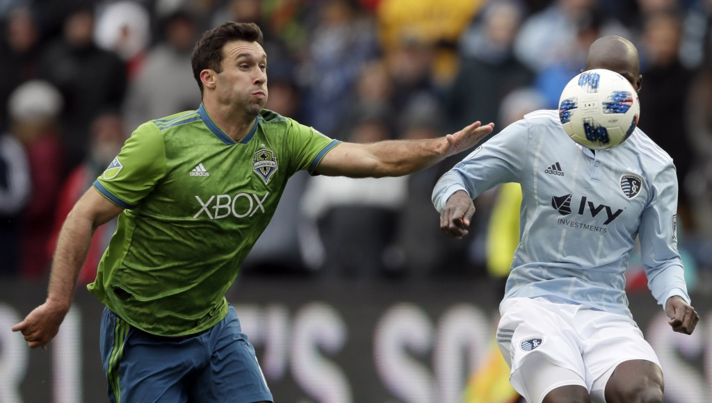 Seattle Sounders defender Will Bruin, left, tries to catch Sporting Kansas City defender Ike Opara, right, during the first half of an MLS soccer matc