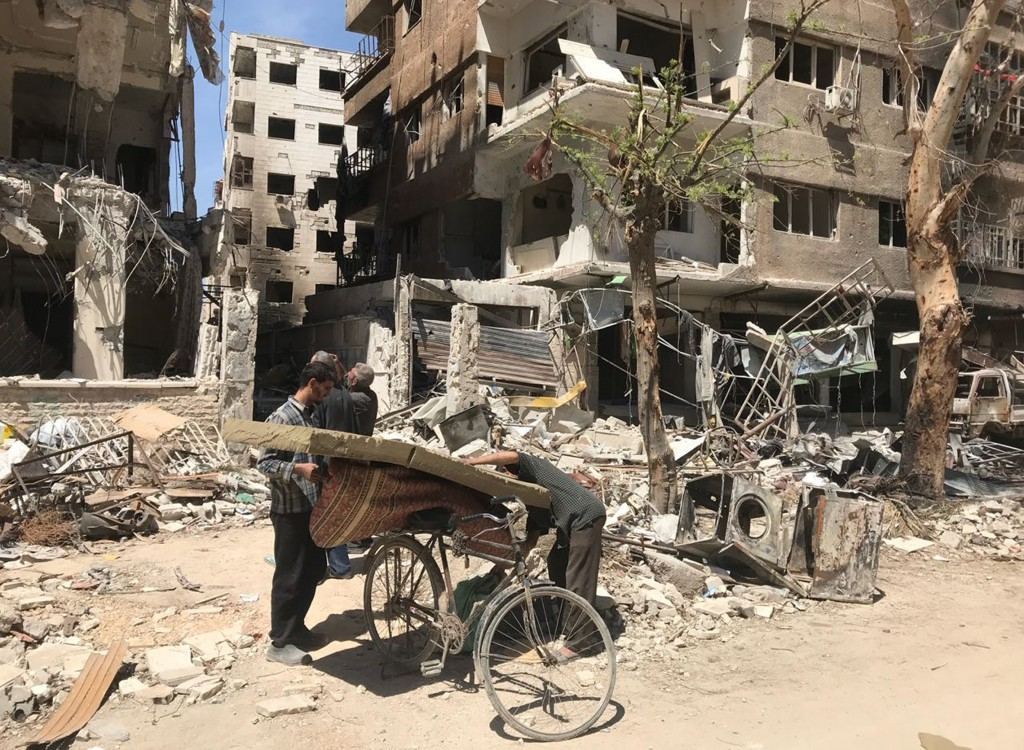 Men load a carpet and mattress on to a bicycle in front of damaged buildings in the town of Douma, the site of a suspected chemical weapons attack, ne