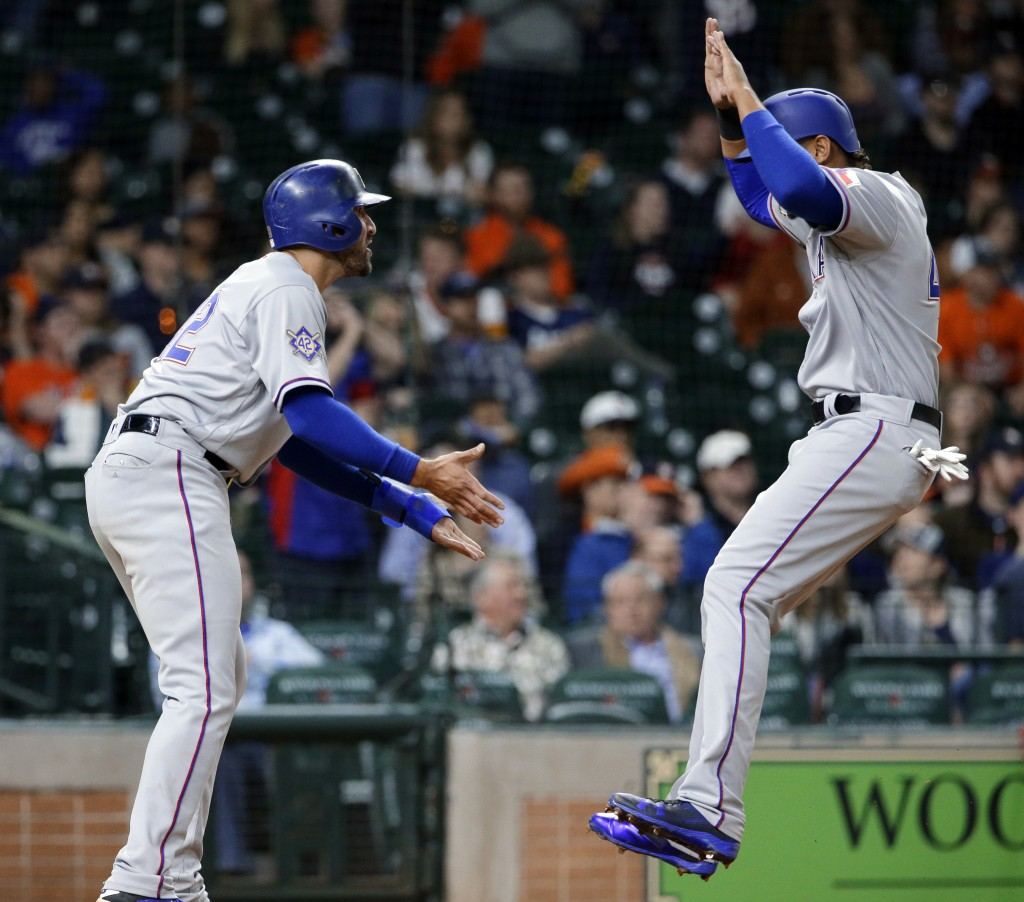 Texas Rangers' Joey Gallo, left, and Ronald Guzman celebrate at the plate after scoring on a double by Robinson Chirinos, making the score 3-1, in the