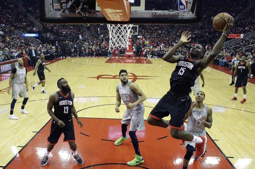 Houston Rockets' Clint Capela shoots over Minnesota Timberwolves' Jeff Teague (0) and Karl-Anthony Towns (32) during the first half in Game 1 of a fir