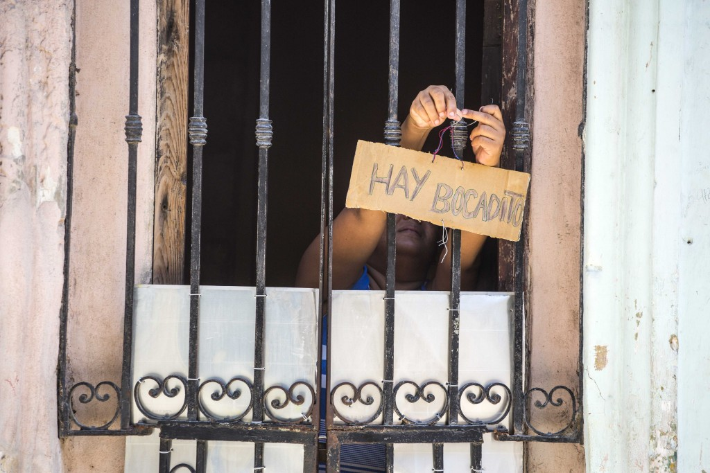 """FILE - In this May 24, 2016 file photo, a woman hangs a sign on her front door that reads in Spanish """"There's sandwiches"""" in Havana, Cuba. Cuba has ne"""