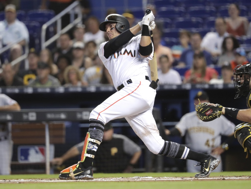 Miami Marlins' Miguel Rojas follows through on a single during the first inning of a baseball game against the Pittsburgh Pirates, Sunday, April 15, 2