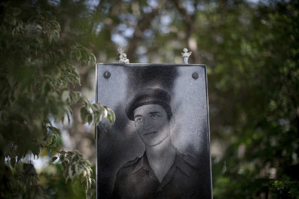 A portrait of Israeli soldier Cpl. Sergey Rubinstein Pukyev placed on his grave at Kiryat Shaul military cemetery on the eve of memorial Day in Tel Av