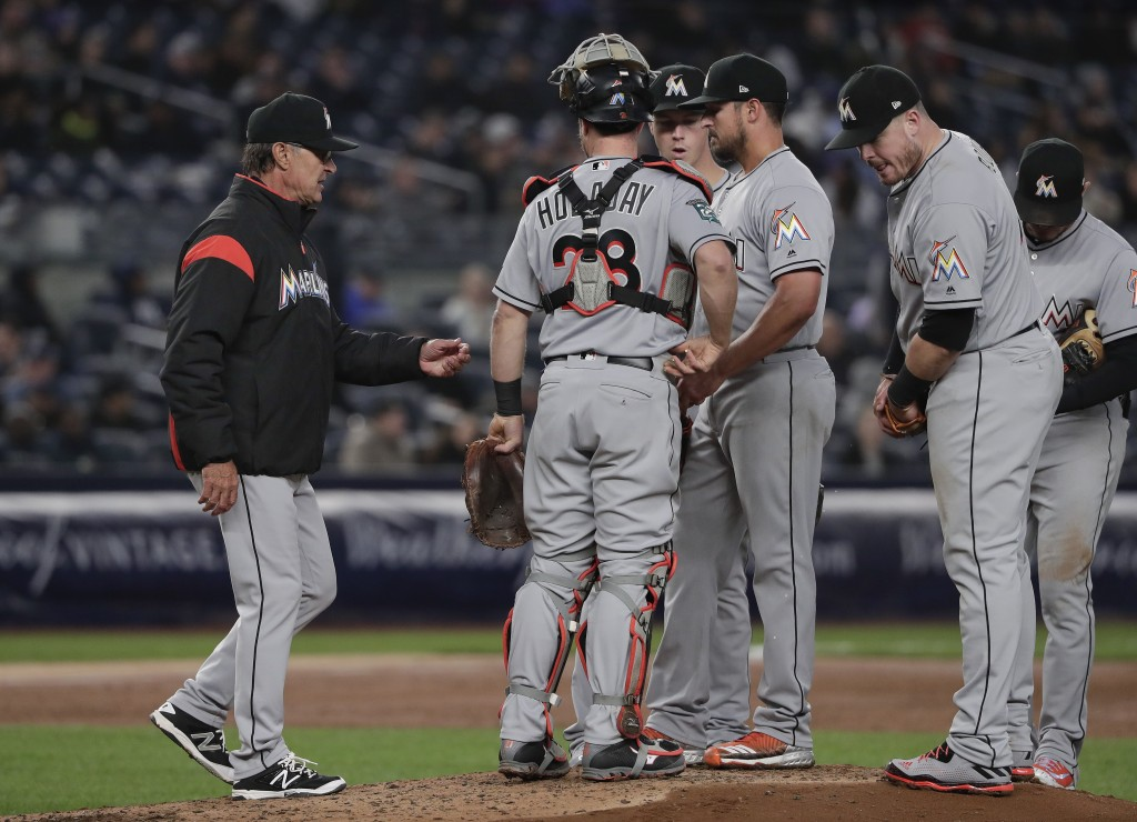 Miami Marlins manager Don Mattingly, left, approaches the mound to relieve pitcher Caleb Smith, center, during the third inning of a baseball game aga