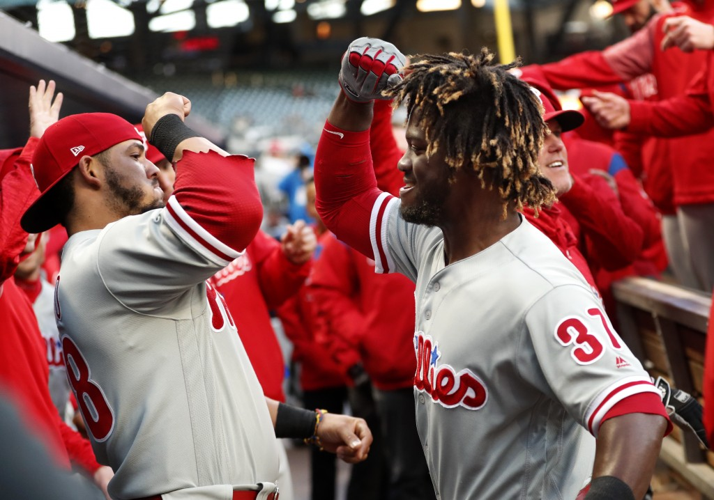 Philadelphia Phillies' Odubel Herrera (37) celebrates in the dugout with Jorge Alfaro (38) after hitting a solo-home run in the first inning of a base