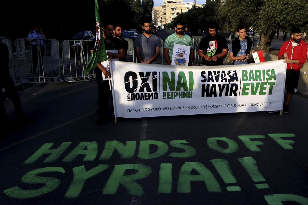 """Protestors with a banner reading in Greek """"NO to the War"""", """"Yes in Peace"""" during a protest against the airstrikes on suspected chemical weapons sites"""