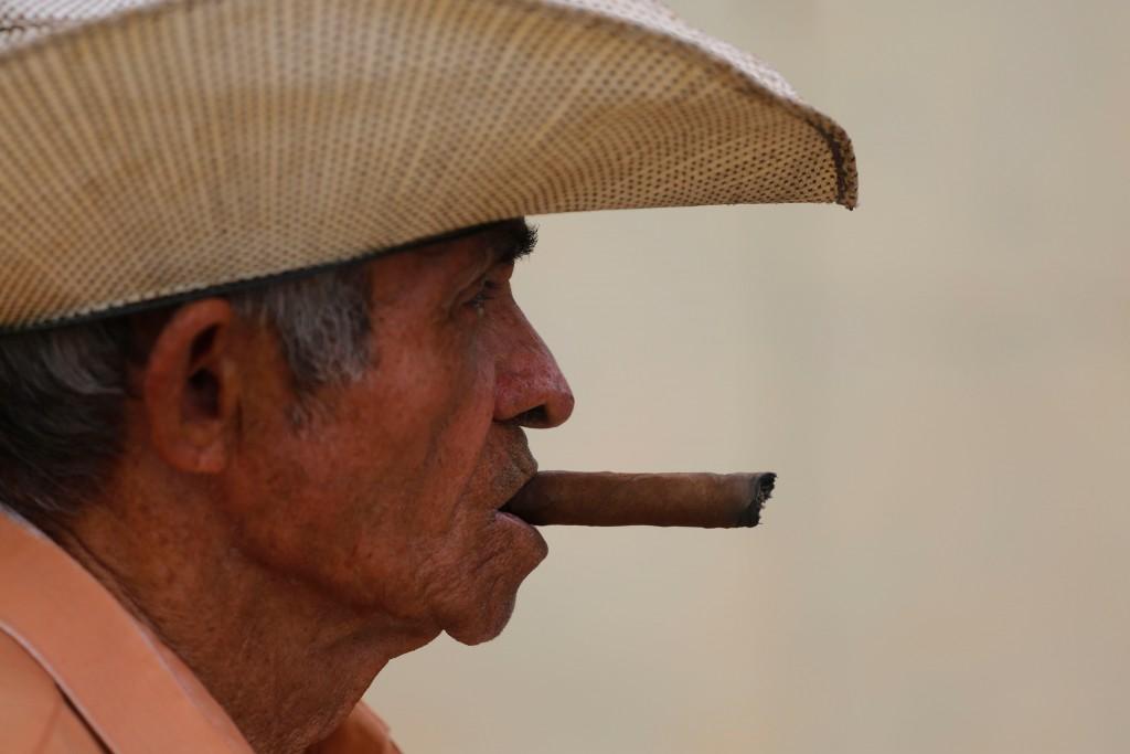 In this April 1, 2018 photo, Edelio Jimenez Santana smokes a cigar in the Vigia neighborhood of Santa Clara, Cuba. The man who is expected to be Cuba'