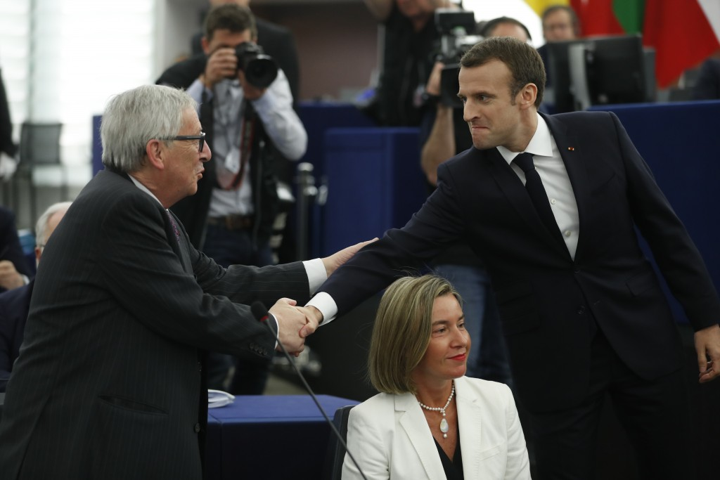 French President Emmanuel Macron, right, shakes hands with European Commission President Jean-Claude Juncker at the European Parliament in Strasbourg,