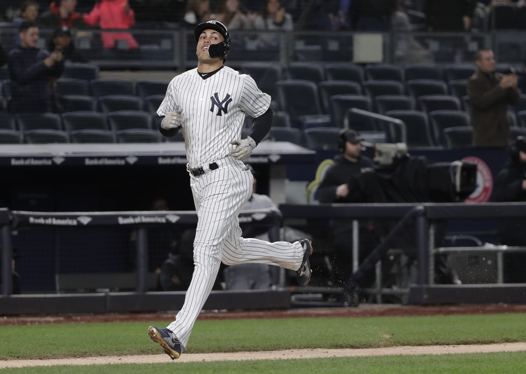 New York Yankees' Giancarlo Stanton runs home on a two-run home run by Didi Gregorius during the fourth inning of a baseball game against the Miami Ma