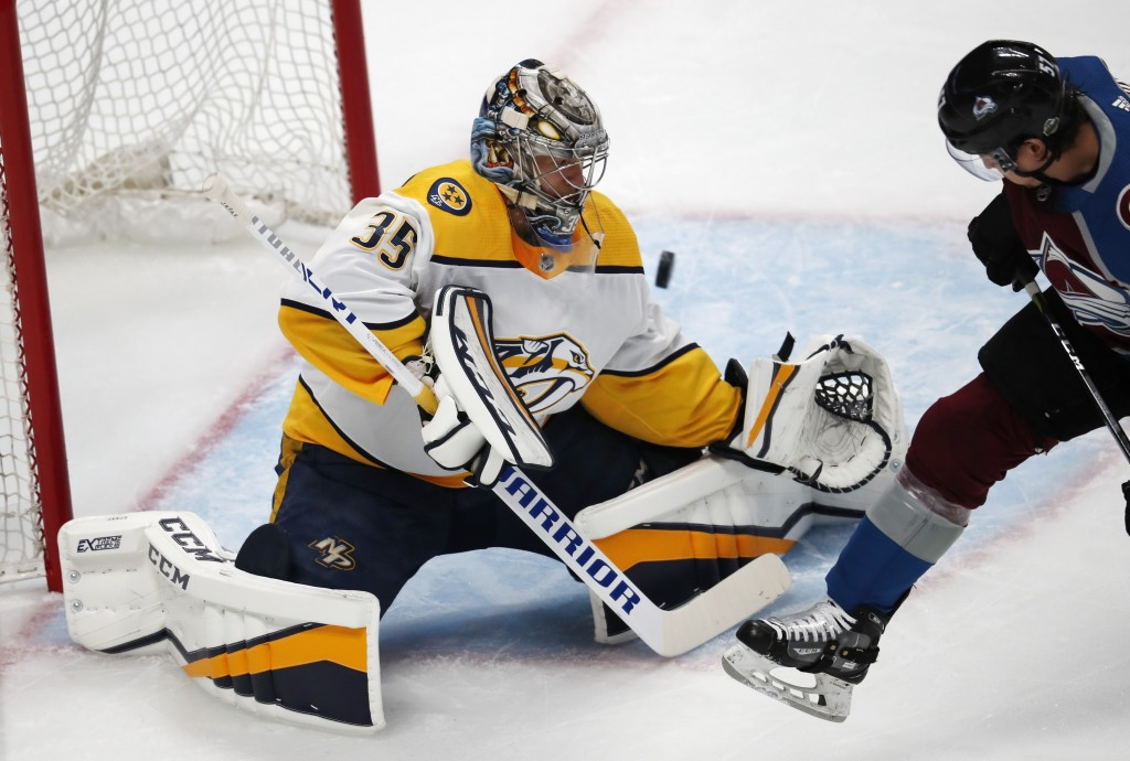 Nashville Predators goaltender Pekka Rinne, left, deflects a shot off the stick of Colorado Avalanche left wing Gabriel Bourque in the first period of