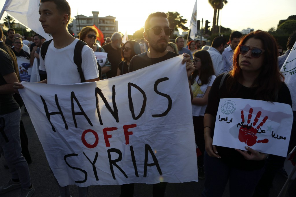 """Protestors holds a banner reading """"Hands off Syria"""" during a protest against the airstrikes on suspected chemical weapons sites in Syria, outside of t"""