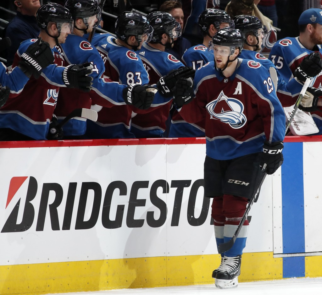 Colorado Avalanche center Nathan MacKinnon, front, is congratulated after scoring a goal against the Nashville Predators as he passes the team box in