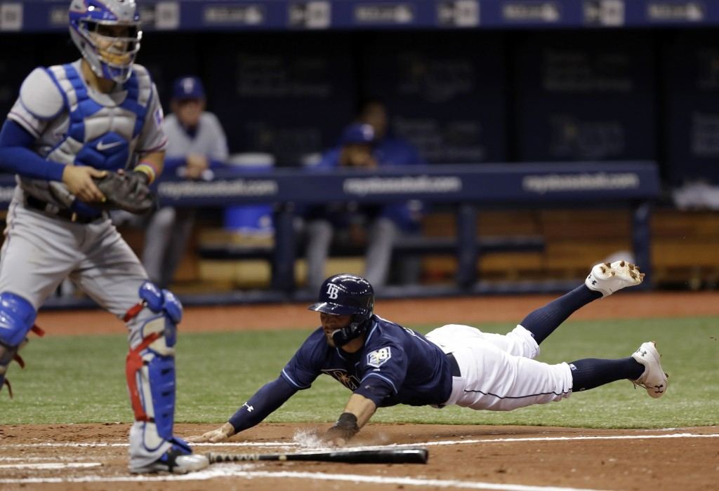 Tampa Bay Rays' Johnny Field, right, dives home in front of Texas Rangers catcher Robinson Chirinos to score on a fielder's choice by Joey Wendle duri