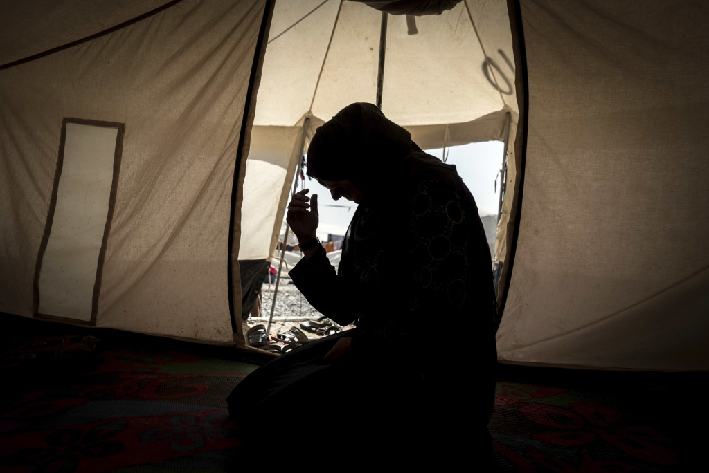 This photo released by Amnesty International on Tuesday, April 17, 2018 shows 33-year-old mother of six, Zahra, inside her tent in Salamiya camp for i