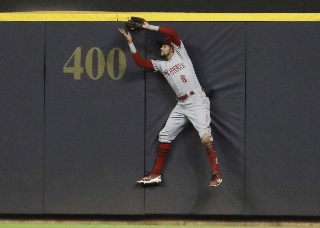 Cincinnati Reds' Billy Hamilton makes a catch at the wall of a ball hit by Milwaukee Brewers' Domingo Santana during the sixth inning of a baseball ga