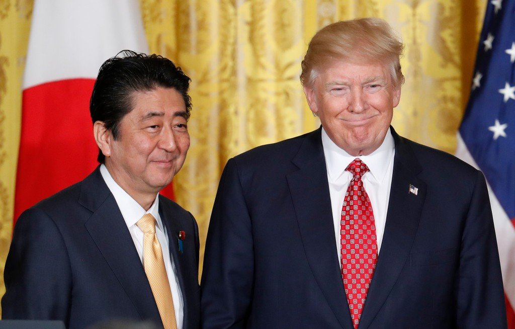 FILE - In this Feb. 10, 2017, file photo, U.S. President Donald Trump, right, and Japanese Prime Minister Shinzo Abe stand on stage together at the co