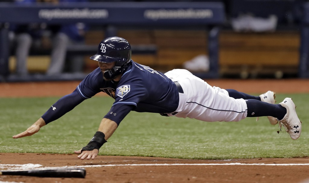 Tampa Bay Rays' Johnny Field dives home to score on a fielder's choice by Joey Wendle during the second inning of a baseball game against the Texas Ra