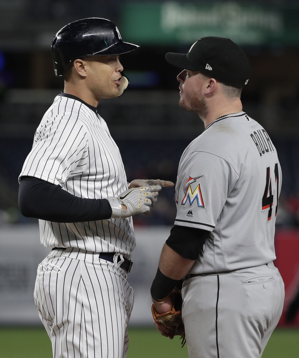 New York Yankees' Giancarlo Stanton, left, speaks with Miami Marlins first baseman Justin Bour (41) after walking during the fourth inning of a baseba