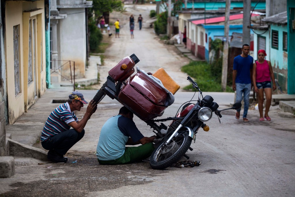 In this April 1, 2018 photo, men repair a motorcycle in the Vigia neighborhood of Santa Clara, Cuba. The man who is expected to be Cuba's next preside