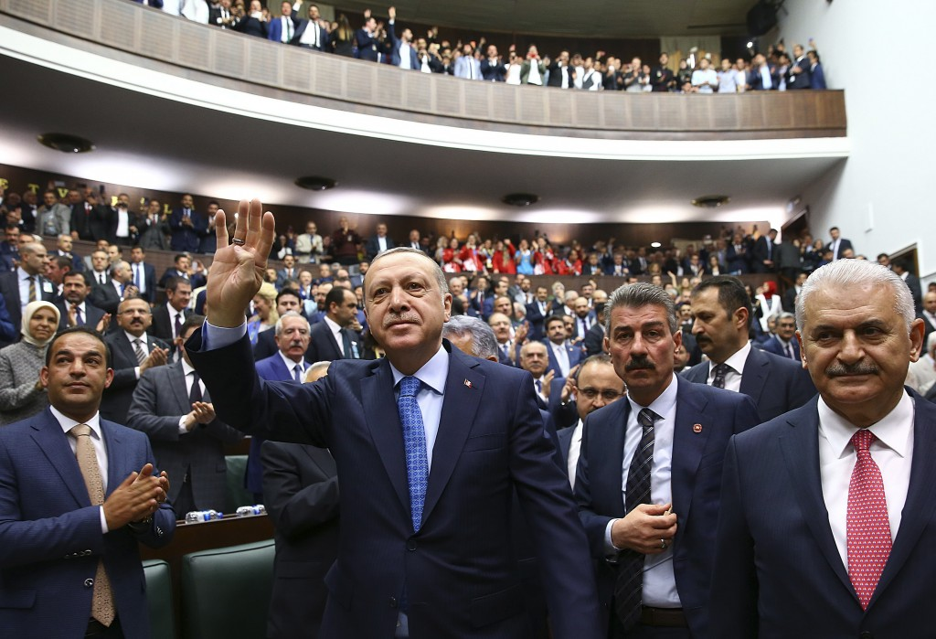 Turkey's President Recep Tayyip Erdogan, centre, accompanied by Prime Minister Binali Yildirim, arrives to deliver a speech at his ruling Justice and