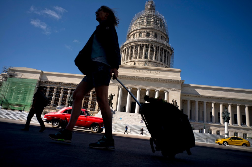FILE - In this Jan. 18, 2018 file photo, a tourist walks with her suitcase in front of the Capitolio in Havana, Cuba. President Donald Trump drew chee
