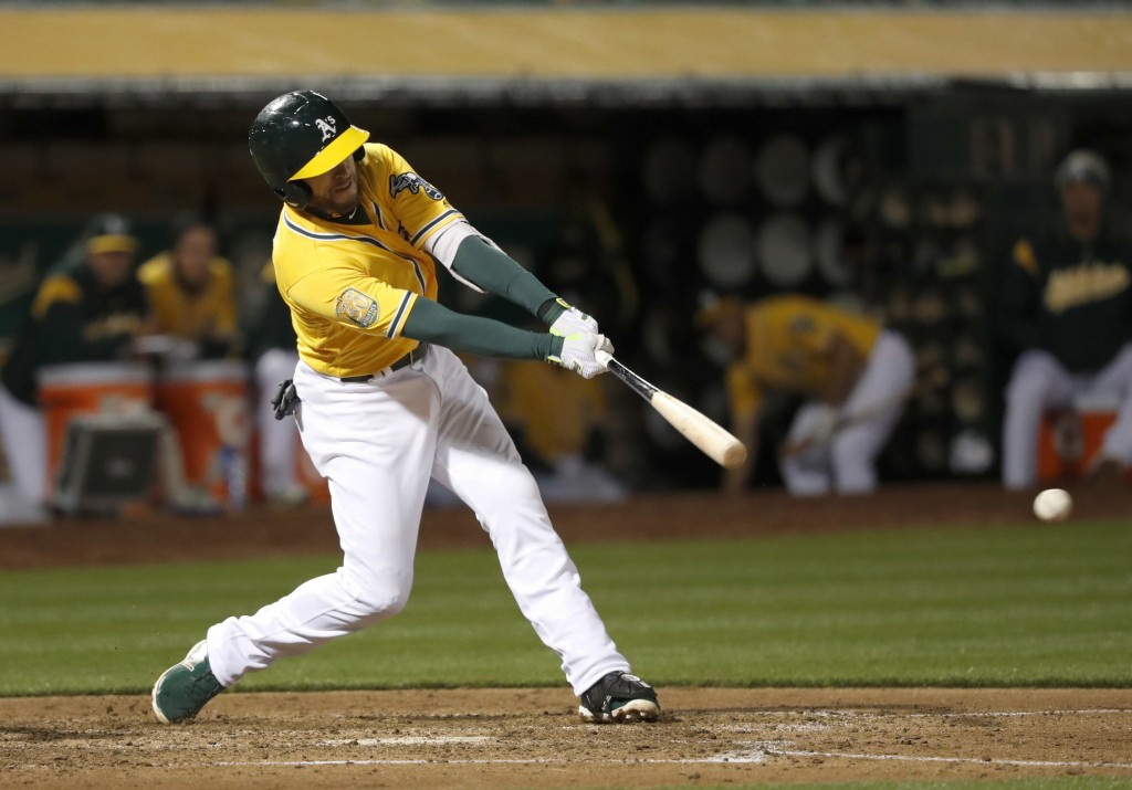 Oakland Athletics' Jed Lowrie hits a single to drive in two runs against the Chicago White Sox during the seventh inning of a baseball game, Monday, A