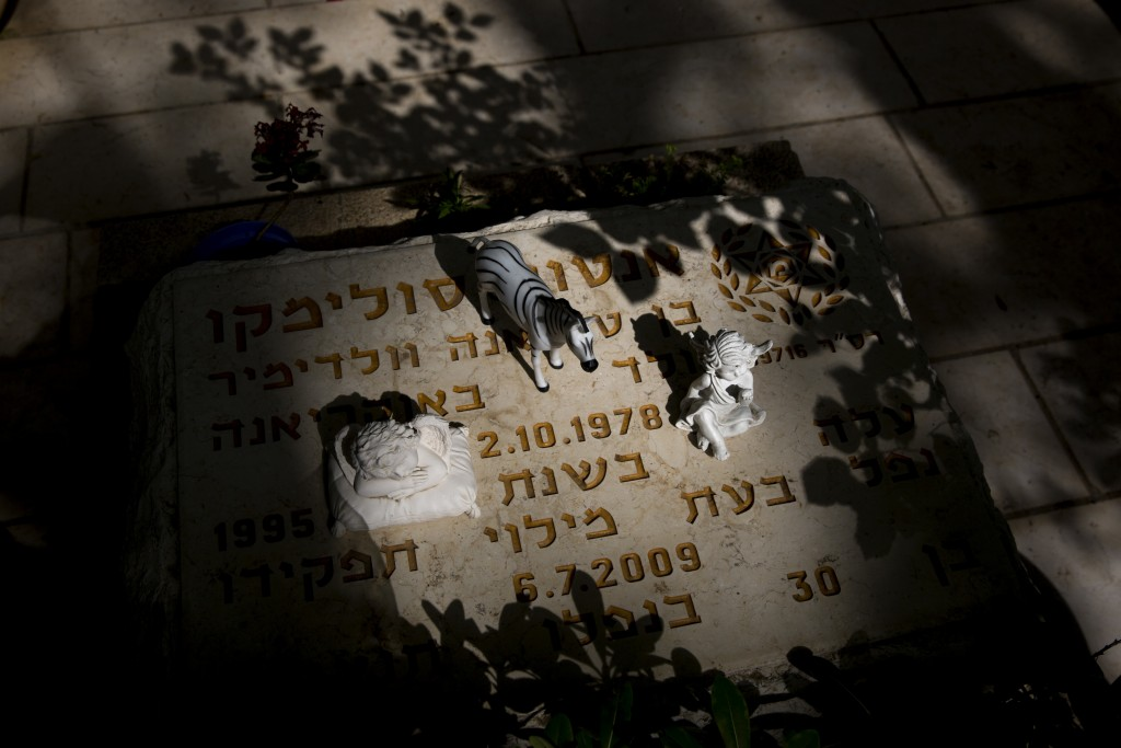 Small items placed on the gravestone of Israeli police officer Anton Solimiko at Kiryat Shaul military cemetery on the eve of memorial Day in Tel Aviv