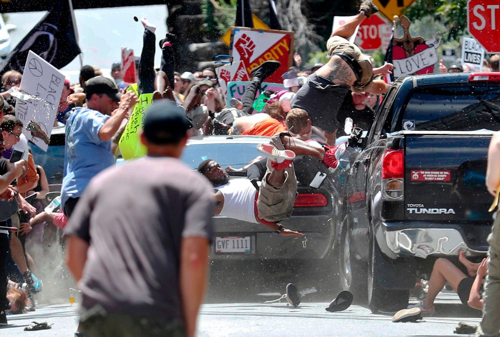 In this Aug. 12, 2017, photo by Ryan Kelly of The Daily Progress, people fly into the air as a car drives into a group of protesters demonstrating aga