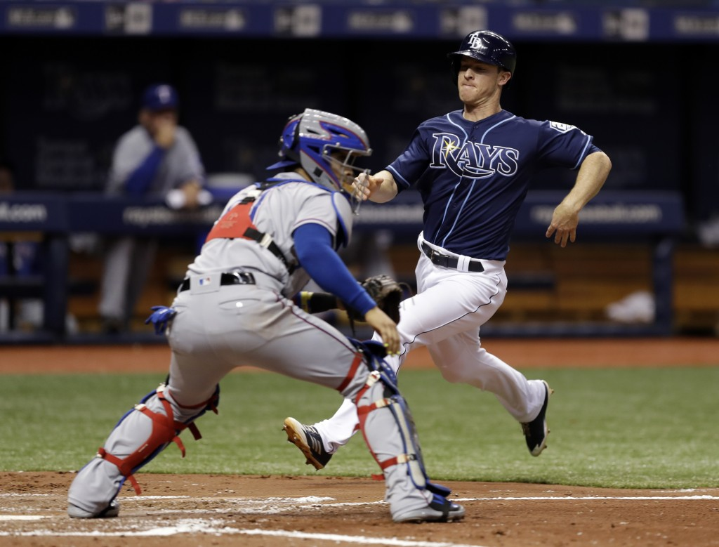 Tampa Bay Rays' Joey Wendle, right, scores in front of Texas Rangers catcher Robinson Chirinos on an RBI single by Carlos Gomez during the second inni