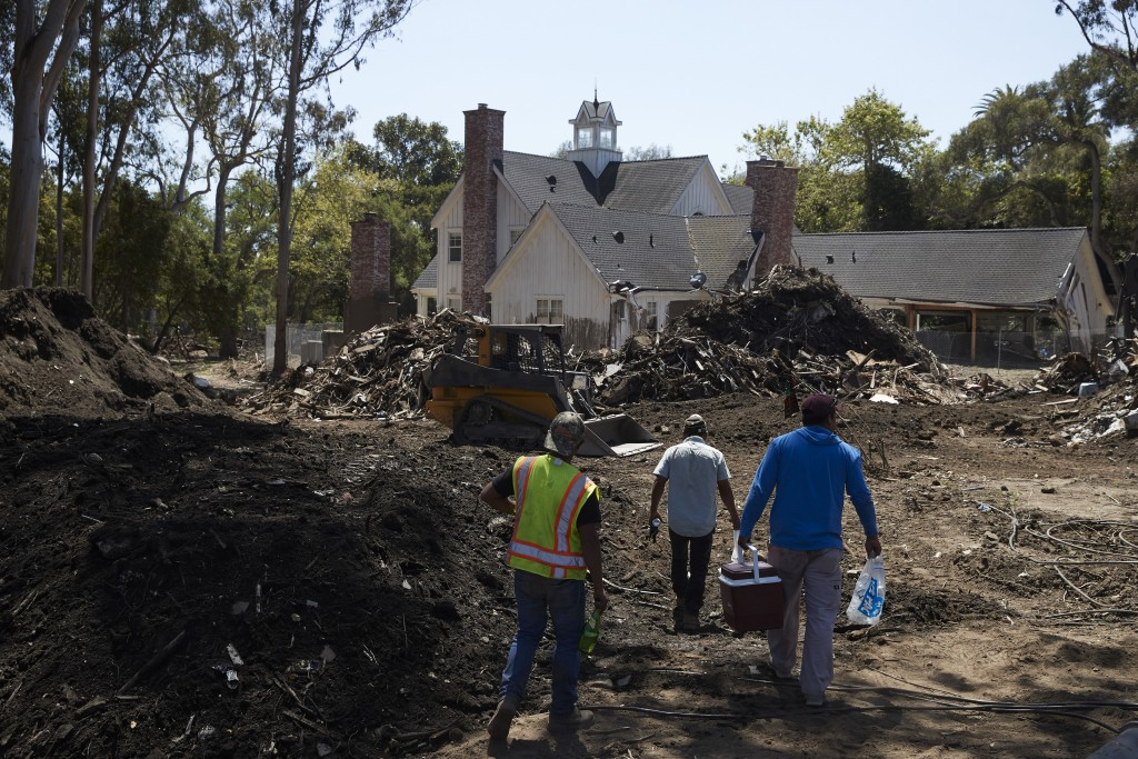 In this Wednesday, April 11, 2018, photo, workers walk past a pile of mud and debris outside a home heavily damaged by a mudslide in Montecito, Calif.