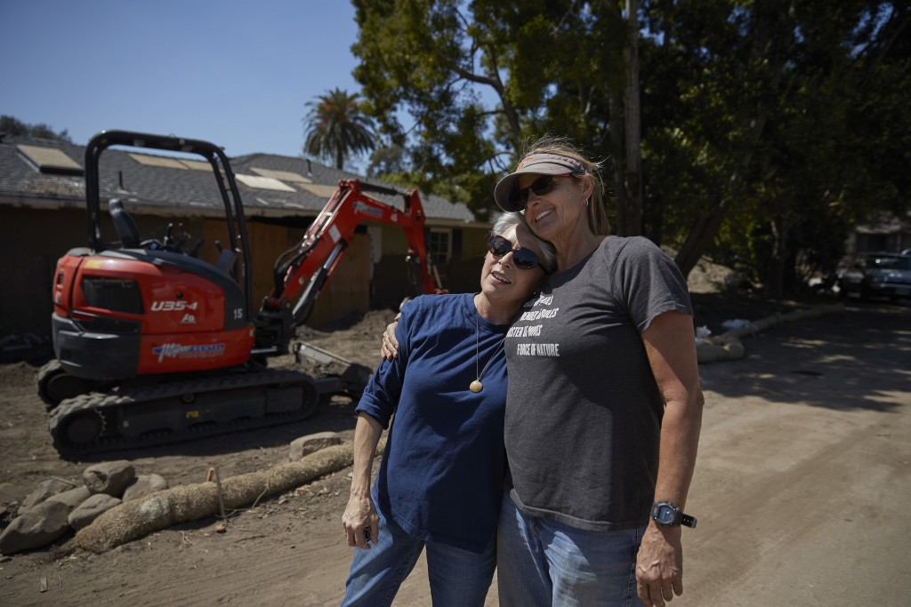 In this Wednesday, April 11, 2018, photo, mudslide survivor Mari Mitchel, left, is hugged by contractor Ann Burgard, who found Mitchel's jewelry, outs