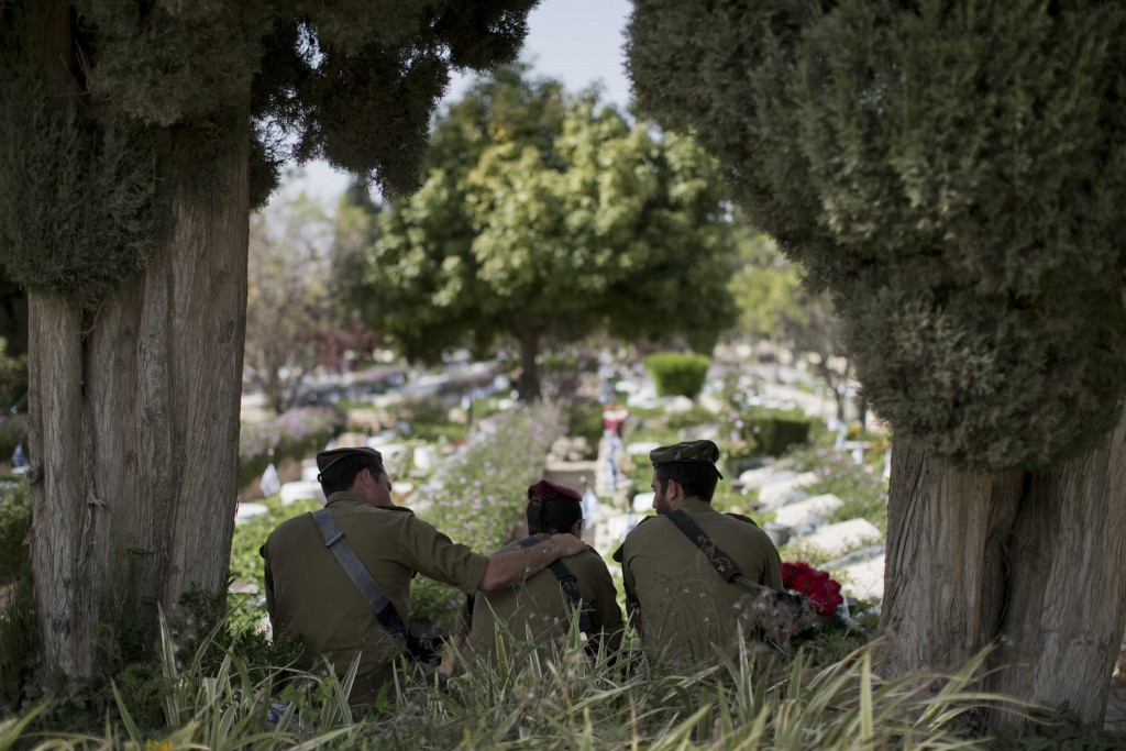 Israeli soldiers visit in Kiryat Shaul military cemetery on the eve of memorial Day, in Tel Aviv, Israel, Tuesday, April 17, 2018. Israel marks the an