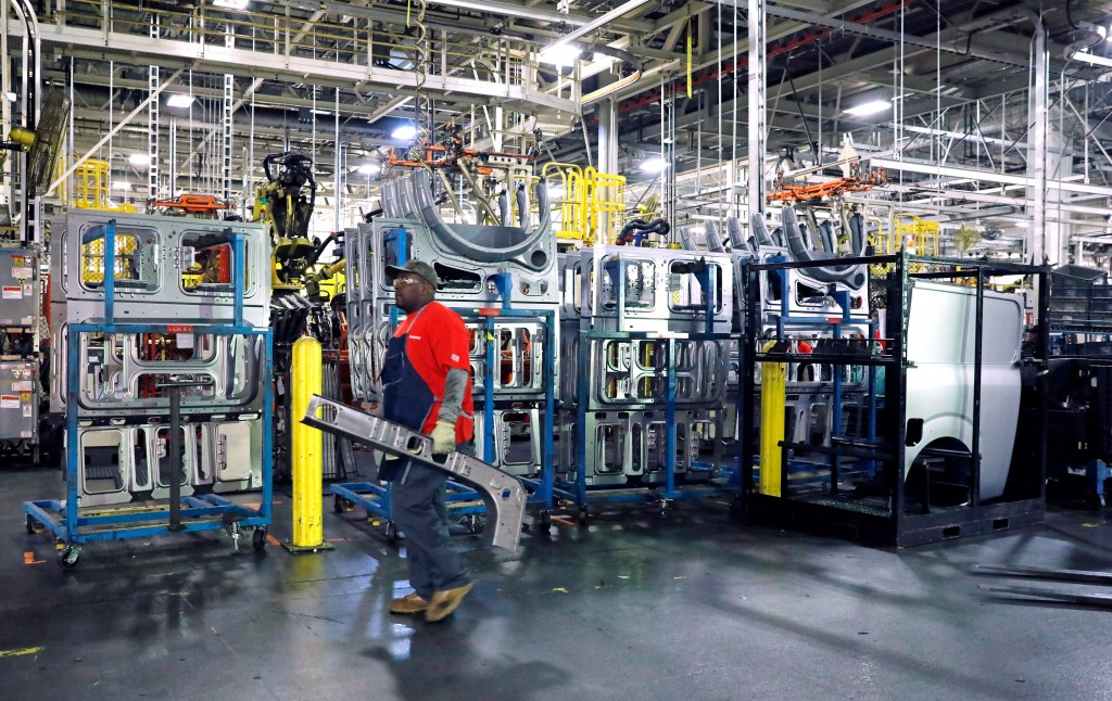 FILE- In this March 19, 2018, file photo a line technician walks past window panels near the NV Commercial Van assembly line at the Nissan Canton Asse