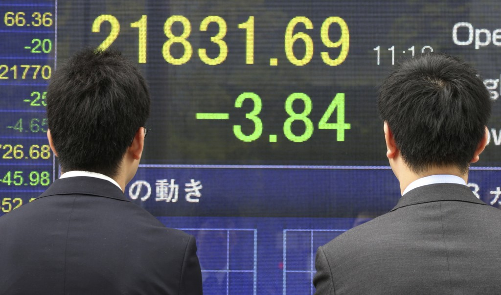 Passers-by look at an electronic stock board of a securities firm showing Japan's benchmark Nikkei 225 in Tokyo, Tuesday, April 17, 2018. Asian shares