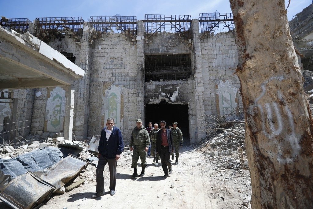Russian military police officers check a weapons factory left behind by members of the Army of Islam group, in the town of Douma, the site of a suspec