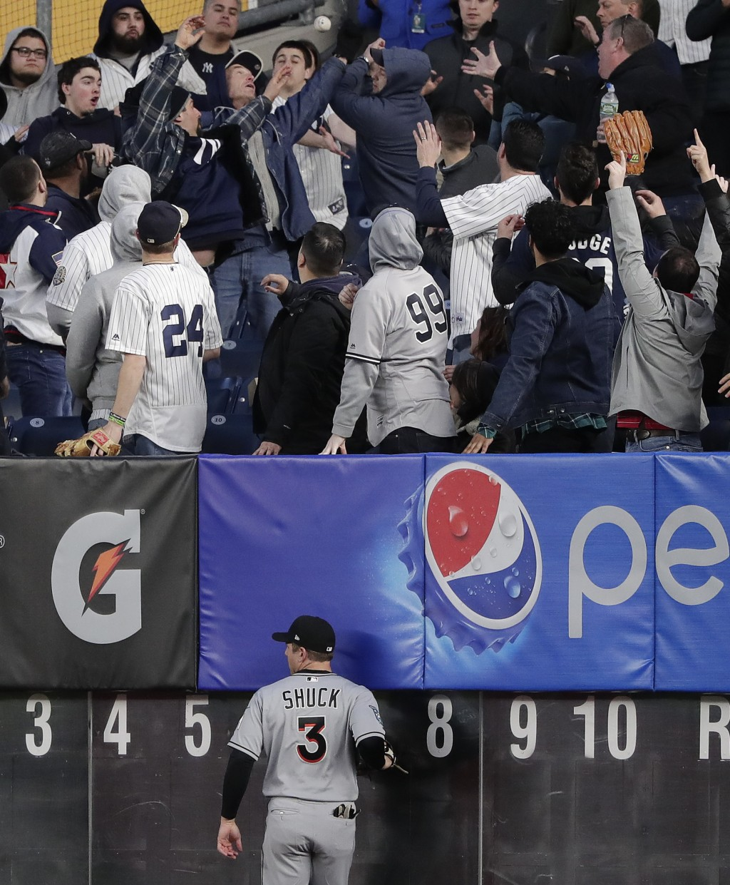 Miami Marlins right fielder J.B. Shuck (3) watches as fans grab at a solo home run by New York Yankees' Aaron Judge during the second inning of a base
