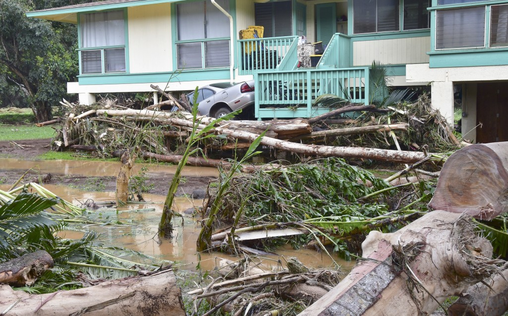 In this Sunday, morning, April 15, 2018 photo, a car is wedged between a house and debris in Anahola, Hawaii, after the Anahola River broke its banks