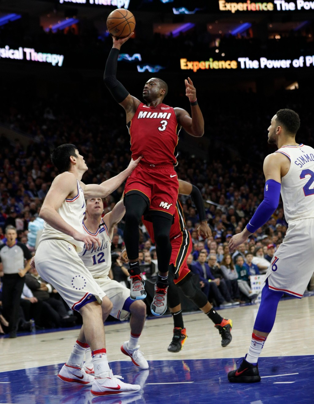 Miami Heat's Dwyane Wade, right, shoots with Philadelphia 76ers' T.J. McConnell, center, and Ersan Ilyasova, left, of Turkey, defend during the first