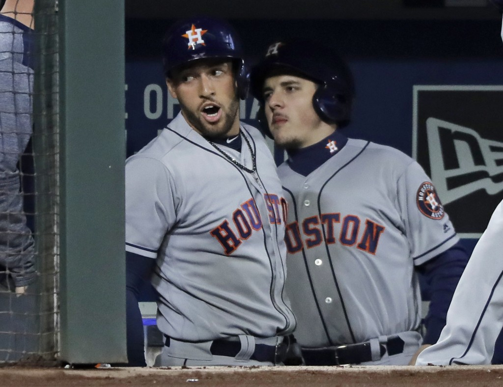 Houston Astros' George Springer, left, reacts in the dugout after he hit a solo home run against the Seattle Mariners in the first inning of a basebal