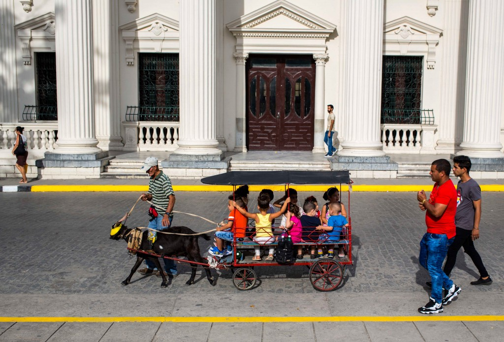 In this April 1, 2018 photo, children ride a goat-pulled-cart around the main square of Santa Clara, Cuba. The man who is expected to be Cuba's next p