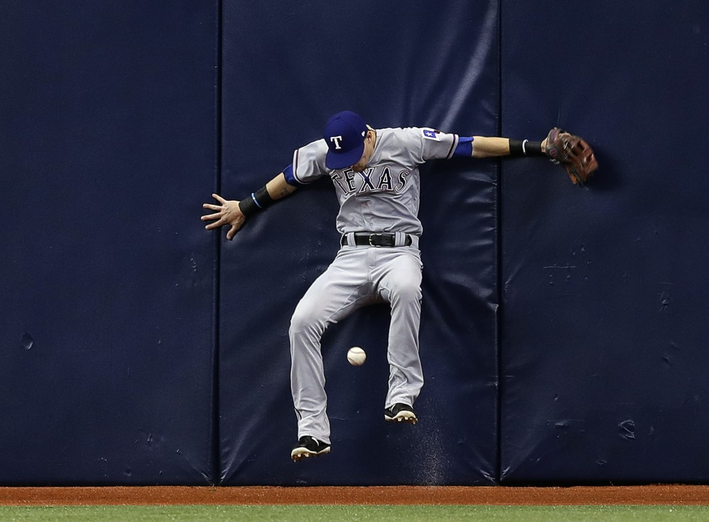 Texas Rangers center fielder Carlos Tocci crashes into the wall chasing a double by Tampa Bay Rays' Wilson Ramos during the sixth inning of a baseball