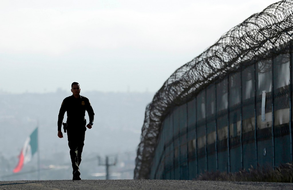 FILE - In this June 22, 2016 file photo, Border Patrol agent Eduardo Olmos walks near the secondary fence separating Tijuana, Mexico, background, and