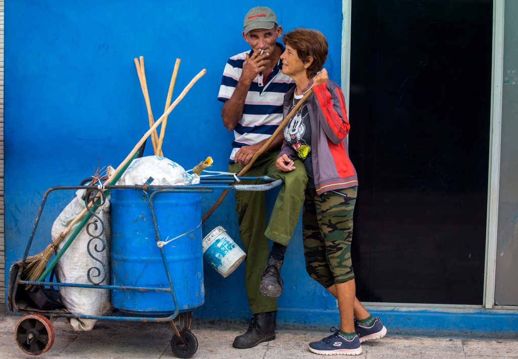 In this April 3, 2018 photo, street cleaners take a break as they work on the main boulevard in Holguin, Cuba. In 2003, Miguel Mario Diaz-Canel Bermud