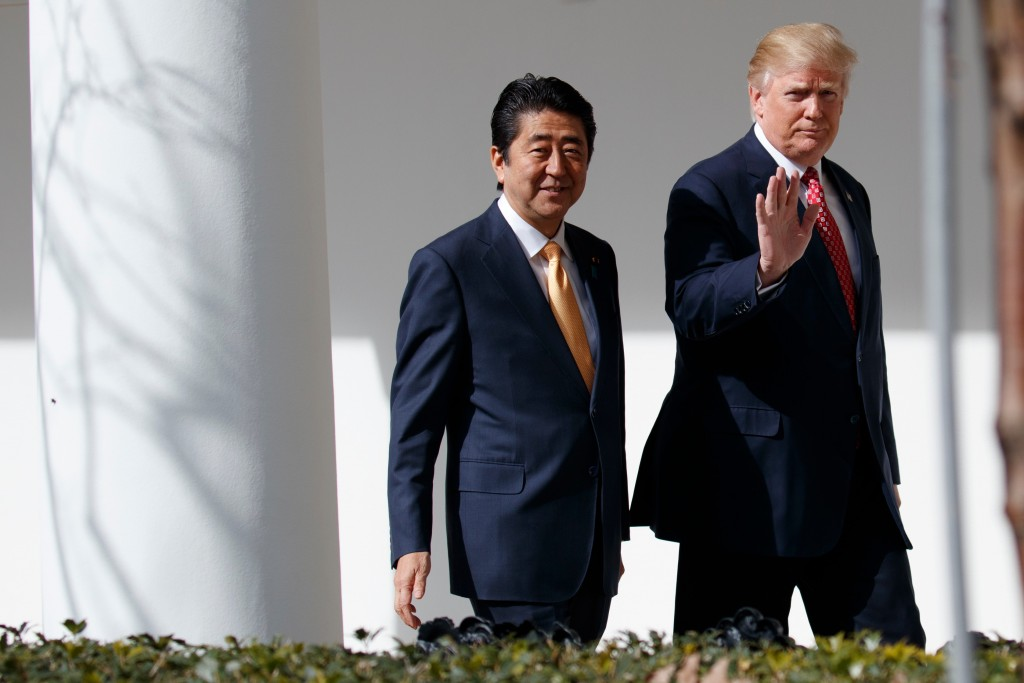 FILE - In this Feb. 10, 2017, file photo,  Japanese Prime Minister Shinzo Abe, left, walks with U.S. President Donald Trump for a news conference at t