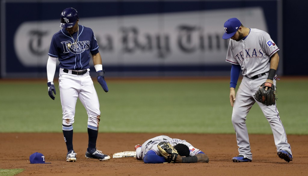 Texas Rangers shortstop Jurickson Profar, center, lies injured on the field after colliding with Tampa Bay Rays' Mallex Smith, left, at second base du