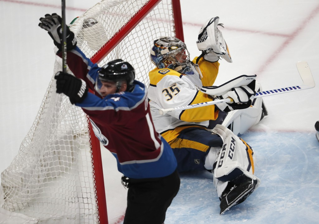 Nashville Predators goaltender Pekka Rinne, back, drops to the ice after missing a shot off the stick of Colorado Avalanche left wing Blake Comeau for