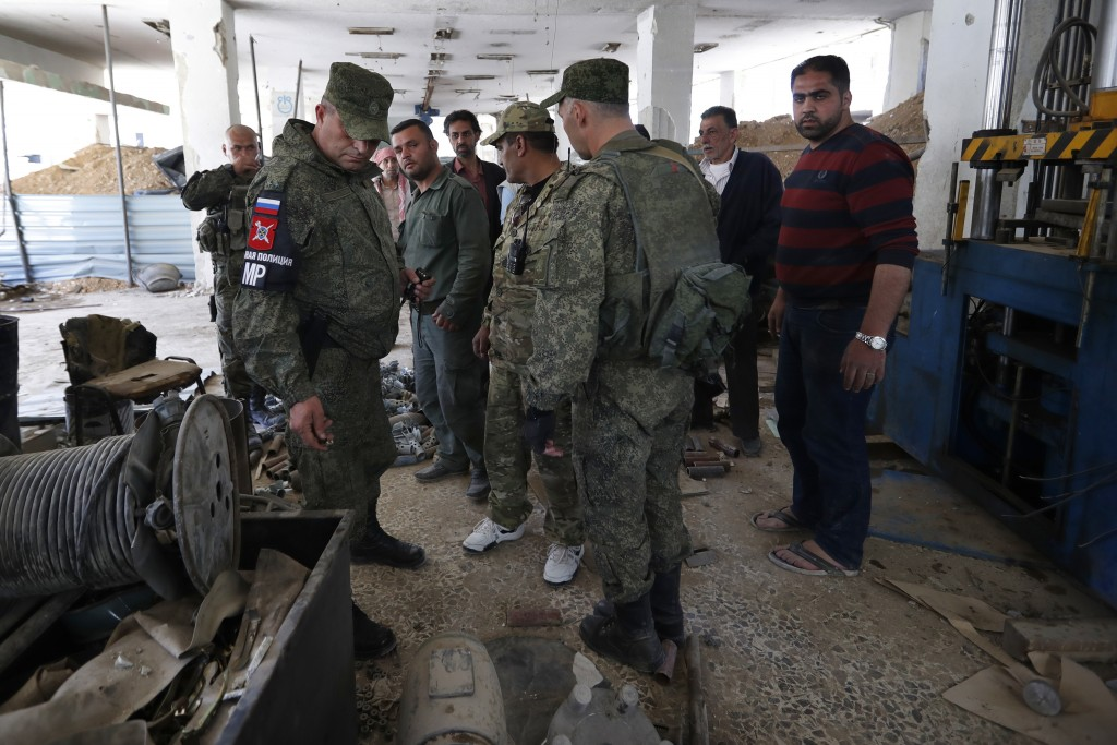 Russian military police officers check weapons left behind by members of the Army of Islam group in a factory produced weapons, in the town of Douma,