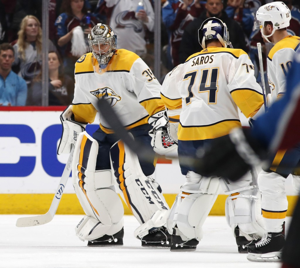 Nashville Predators goaltender Pekka Rinne, left, skates back to the team box as he is replaced by backup goaltender Juuse Saros after giving up a goa