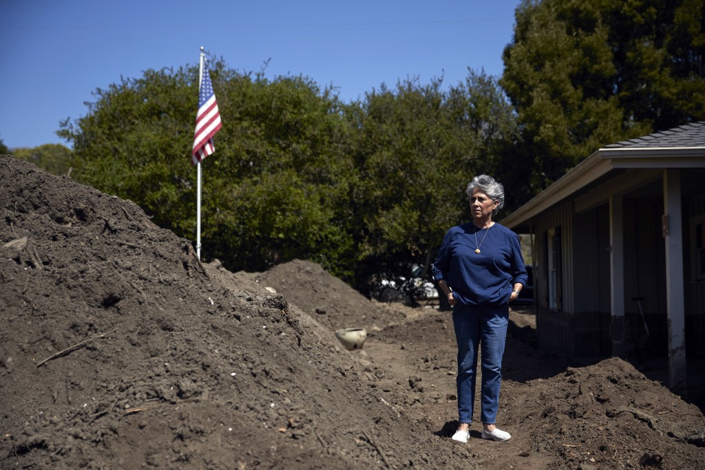 In this Wednesday, April 11, 2018, photo, mudslide survivor Mari Mitchel pauses for photos next to a pile of dirt outside her home that was devastated